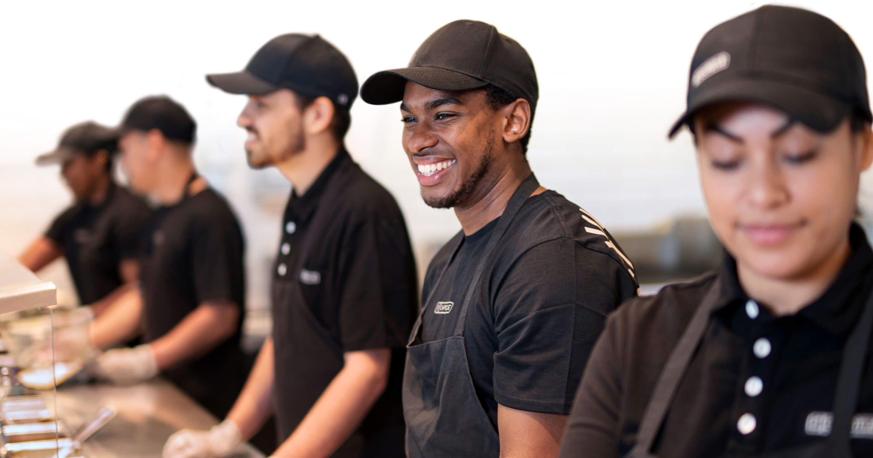 4 chipotle team members smiling